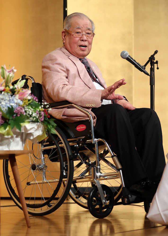 車いす姿で講演する野村氏(撮影・久冨木 修)