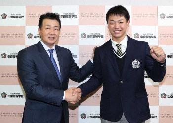 写真:与田監督(左)と笑顔で握手し、ガッツポーズする中京大中京・高橋