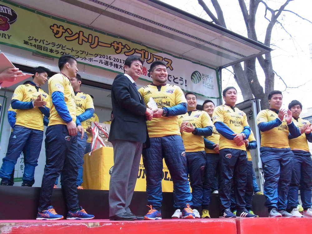 東京都府中市で行われた市主催のサントリー優勝報告会で、高野律雄市長(中央左)から副賞を贈られ笑顔 ...