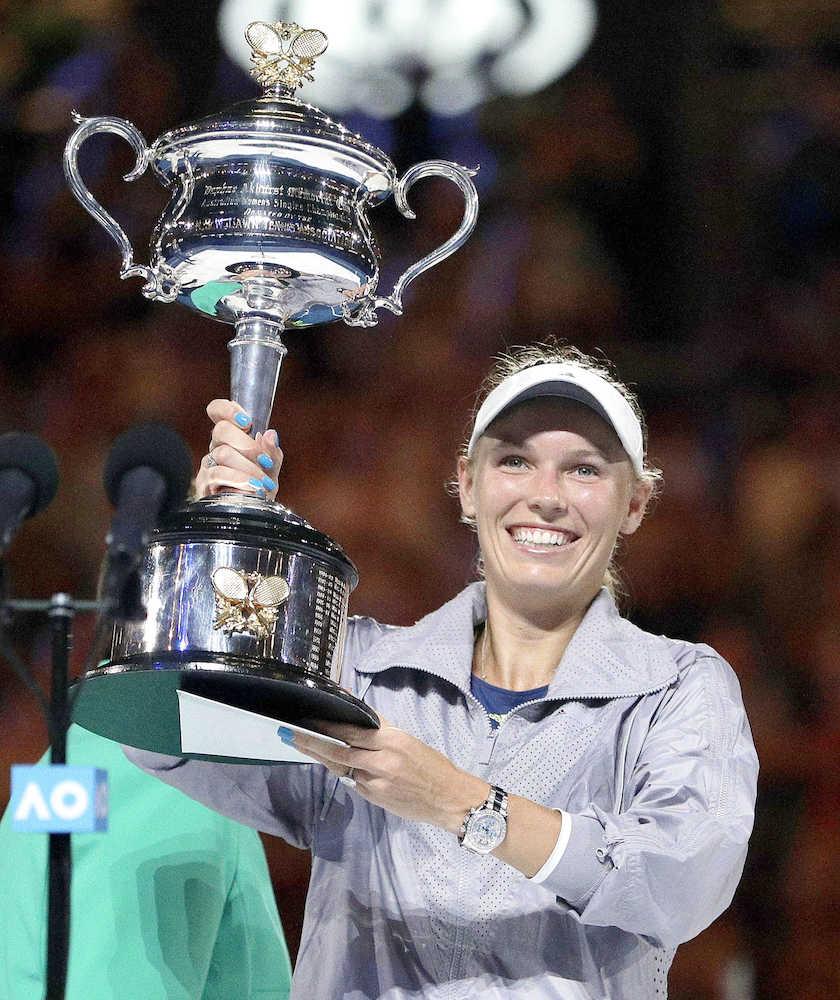 全豪テニス女子シングルスで優勝し、笑顔でトロフィーを掲げるキャロライン・ウォズニアッキ